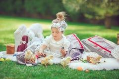 Счастливый ребенок сидит на взглядах луга к украшению пасхи Стоковые Изображения