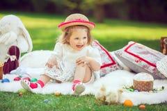 Счастливый ребенок сидит на луге вокруг украшения пасхи Стоковое Изображение RF