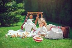 Счастливый ребенок сидит на луге вокруг украшения пасхи Стоковые Фото