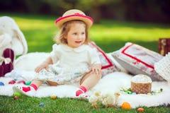 Счастливый ребенок сидит на луге вокруг украшения пасхи Стоковые Изображения RF