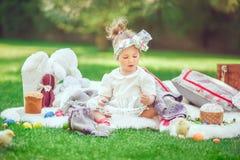 Счастливый ребенок сидит на луге вокруг украшения пасхи Стоковая Фотография