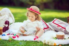 Счастливый ребенок сидит на луге вокруг украшения пасхи Стоковое Фото