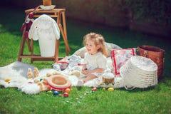 Счастливый ребенок сидит на луге вокруг украшения пасхи Стоковые Фотографии RF