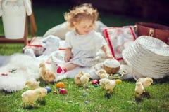 Счастливый ребенок сидит на луге вокруг украшения пасхи Стоковая Фотография RF