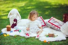 Счастливый ребенок сидит на луге вокруг украшения пасхи Стоковые Изображения