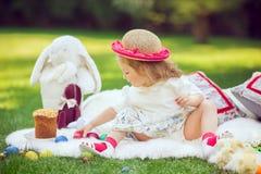 Счастливый ребенок сидит на луге вокруг украшения пасхи Стоковое Изображение