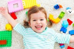 Счастливый ребенок смеясь над и играя с конструктором игрушек стоковое изображение rf