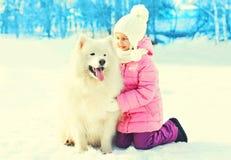 Счастливый ребенок с белой зимой собаки Samoyed стоковое изображение