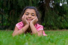 Счастливый ребенок усмехаясь в траве во время лета Стоковые Фото