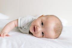 Счастливый ребёнок лежа вниз на белой кровати Стоковые Изображения