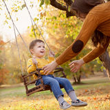 Счастливый ребёнок имея потеху на езде качания на саде день осени Стоковая Фотография RF