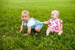 Счастливый ребёнок 2 и время девушки 9 месяцев старых, сидящ на траве и взаимодействуют, говорят, смотрят один другого Стоковое Изображение RF