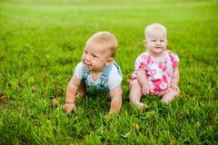 Счастливый ребёнок 2 и время девушки 9 месяцев старых, сидящ на траве и взаимодействуют, говорят, смотрят один другого Стоковые Изображения RF