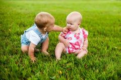 Счастливый ребёнок 2 и время девушки 9 месяцев старых, сидящ на траве и взаимодействуют, говорят, смотрят один другого Стоковое Изображение
