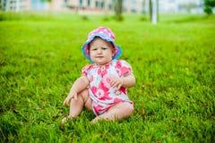 Счастливый ребёнок 2 и время девушки 9 месяцев старых, сидящ на траве и взаимодействуют, говорят, смотрят один другого Стоковые Изображения