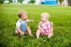 Счастливый ребёнок 2 и время девушки 9 месяцев старых, сидящ на траве и взаимодействуют, говорят, смотрят один другого Стоковая Фотография