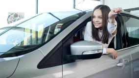 Счастливый ребёнок показывая ключ его нового автомобиля Автоматическое дело, продажа автомобиля, технология и концепция людей - с Стоковые Изображения RF