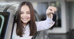 Счастливый ребёнок показывая ключ его нового автомобиля Автоматическое дело, продажа автомобиля, технология и концепция людей - с Стоковое Изображение RF