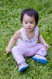 Счастливый ребёнок сидя на траве Стоковые Изображения RF