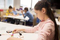 Счастливый робот здания девушки на школе робототехники Стоковое фото RF