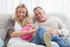 Счастливый родитель щекоча их милую дочь на кресле Стоковые Изображения RF