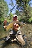Счастливый рыболов с огромной форелью Стоковые Фотографии RF