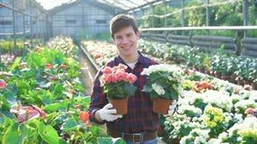 Счастливый садовник держа цветочные горшки и усмехаясь 4K сток-видео