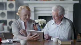 Счастливый симпатичный выбытый планшет пользы пар Они имея потеху в связывать с семьей акции видеоматериалы