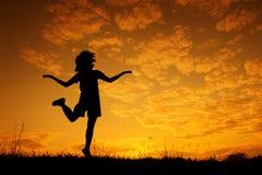 Счастливый силуэт скакать и захода солнца женщины Стоковые Фото