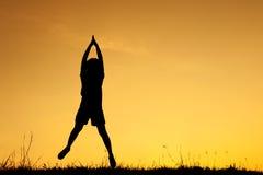 Счастливый силуэт скакать и захода солнца женщины Стоковое фото RF