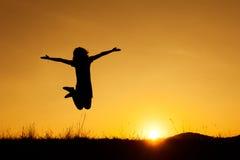 Счастливый силуэт скакать и захода солнца женщины стоковое изображение