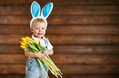 Счастливый смеясь над ребёнок в ушах зайчика с желтыми тюльпанами на wo стоковое фото