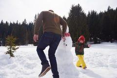 Счастливый снеговик здания семьи Стоковые Изображения RF