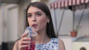 Счастливый, сок молодой женщины выпивая сидя в экзотическом кафе видеоматериал