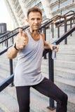 Счастливый спортсмен smiley держа бутылку воды, стоящ на шагах смотря камеру усмехаясь и показывая большой палец руки стоковые фото