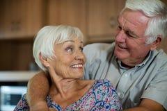 Счастливый старший один другого обнимать пар в кухне Стоковые Изображения