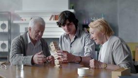 Счастливый старший человек и женщина играя настольную игру с его внуком видеоматериал