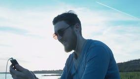 Счастливый стильный молодой человек пишет sms около моря В небе самолет летает выходящ след Красивый человек с акции видеоматериалы