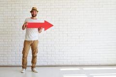 Счастливый стильный человек стоящ и держащ большая красная стрелка Стоковое Изображение