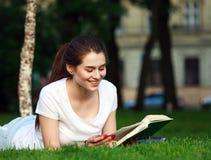 Счастливый студент девушки в парке города читая книгу Стоковое Изображение