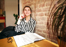 Счастливый студент девушки дома на таблице говоря на телефоне Стоковая Фотография