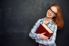 Счастливый студент девушки с стеклами и книгой от классн классного Стоковые Изображения