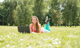 Счастливый студент женщины лежа на траве с компьтер-книжкой Успешная девушка онлайн Красивая молодая женщина с тетрадью в парке н Стоковые Фото