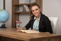 Счастливый студент на библиотеке читая книгу Стоковые Изображения