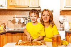 Счастливый сын и мать отрезая пиццу в кухне Стоковая Фотография