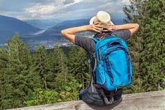 Счастливый туристский рюкзак девушки сидя в австрийской горе Альпов и наслаждаясь летом и природой Стоковые Фото
