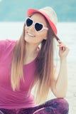Счастливый турист девушки в соломенной шляпе и солнечных очках сидя на пляже, свободном времени на взморье Стоковые Изображения