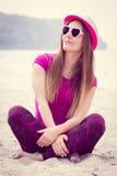 Счастливый турист девушки в соломенной шляпе и солнечных очках сидя на пляже, свободном времени на взморье Стоковая Фотография