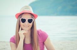 Счастливый турист женщины в соломенной шляпе и солнечных очках сидя на пляже, свободном времени на взморье Стоковые Фотографии RF