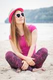 Счастливый турист женщины в соломенной шляпе и солнечных очках сидя на пляже, свободном времени на взморье Стоковое Изображение